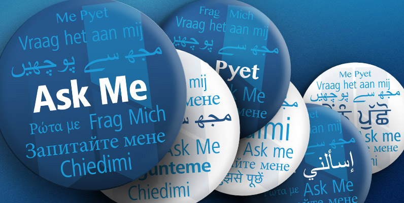 a graphic of a pin button with the text Ask Me and its various translations in other languages