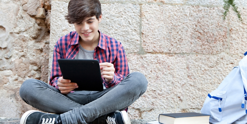 Teen boy reading an eBook on a tablet