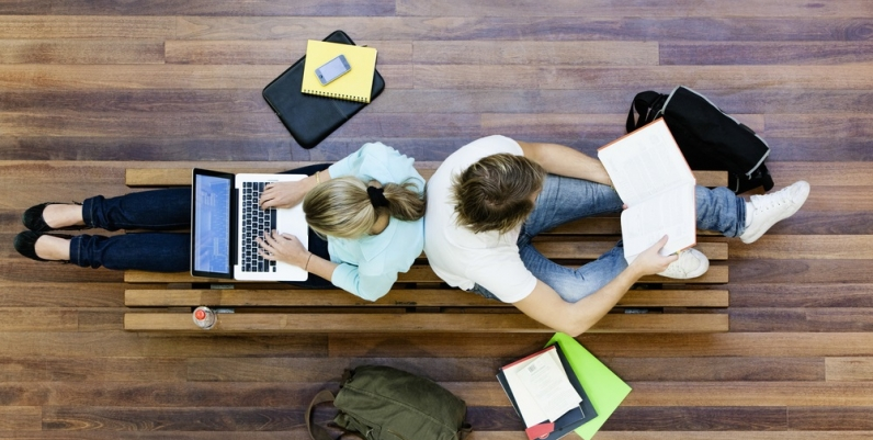 Overhead photo of two teens reading a book and working on a laptop back to back