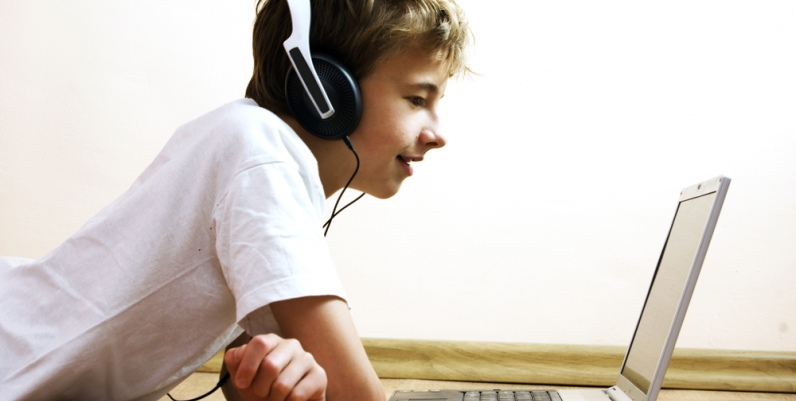 Teen boy using a laptop and wearing headphones