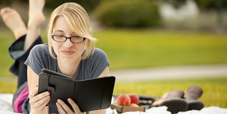 female reading an ebook on a picnic blanket outdoors