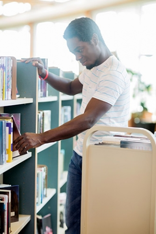 A man placing books on a shelf from a cart.