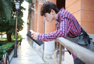 Teenage boy reading a boy outside