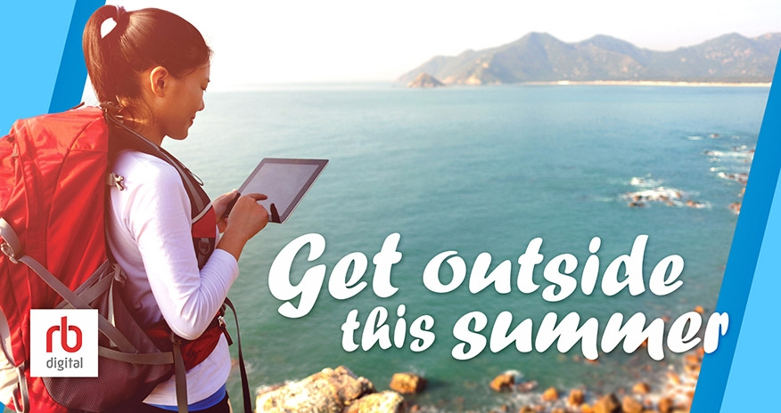 a girl holding a tablet hiking with an ocean view