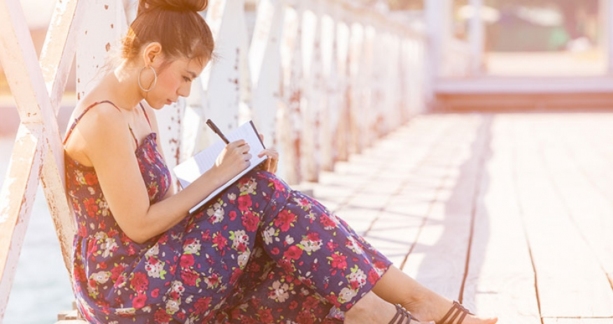 girl sitting on a bridge writing on her notebook